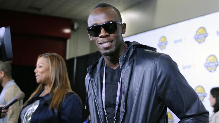 Olympic gold medalist Usain Bolt, right, and singer/actress Queen Latifah arrive at the NBA All-Star celebrity game Friday, Feb. 15, 2013, in Houston. (AP Photo/Pat Sullivan)