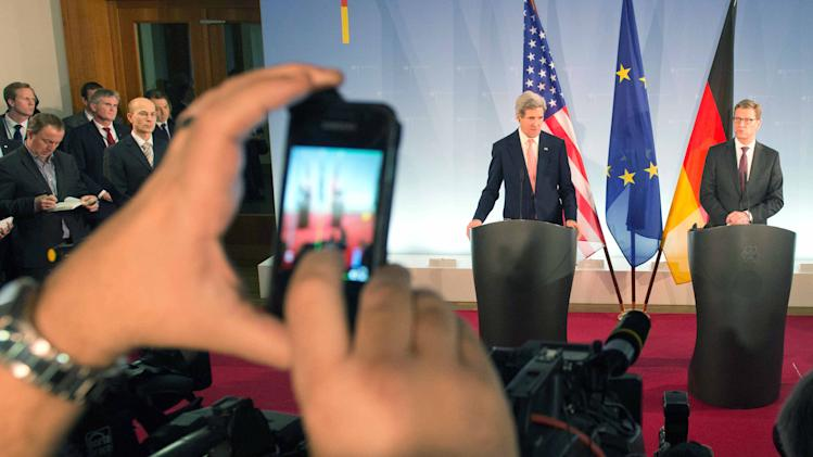 A journalist takes a photo  as  German foreign minister Guido Westerwelle, right,  and  US Secretary of State,John Kerry,  deliver speeches at the Foreign Ministry in Berlin, Germany, Tuesday Feb, 26, 2013. Berlin is the second stop in Kerry's first trip overseas as secretary.  (AP Photo/dpa, Maurizio Gambarini)