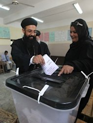 An Egyptian Coptic priest casts his ballot at a polling station in Cairo as Egyptians voted in the country's first free presidential election in May 2012. Many Egyptian Coptic Christians were dismayed by the election victory of president-elect Mohamed Morsi, but they are now preparing to co-exist with the Islamist while also safeguarding their rights