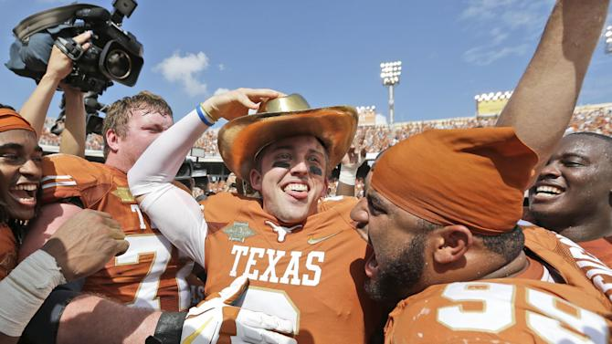 Texas quarterback Case McCoy (6) dons the golden hat trophy as he celebrates with teammate including Desomond Jackson (99) after their 36-20 win over Oklahoma in an NCAA college football game at the Cotton Bowl Saturday, Oct. 12, 2013, in Dallas