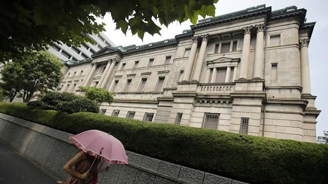 A pedestrian holding an umbrella walks past the Bank of Japan headquarters in Tokyo