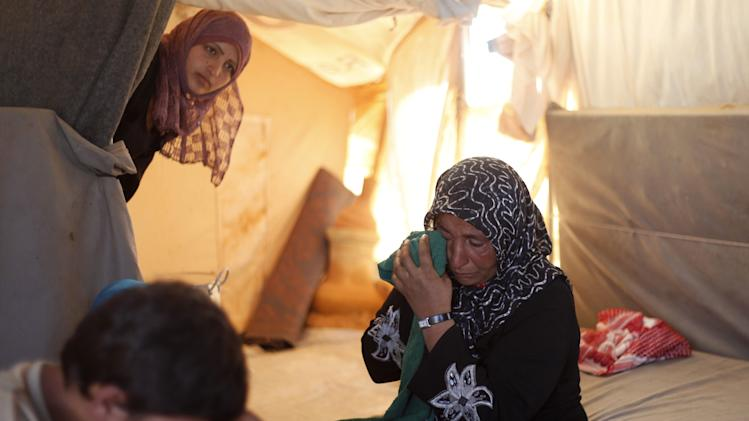 In this Tuesday, Sept. 11, 2012 photo, the 46-year-old wife of farmer Ghassan Baradan, who fled her southern restive border town of Daraa, Syria with her family in July, wipes her eyes as she speaks during an interview at the Zaatari Refugee Camp, in Mafraq, Jordan. Jordan now hosts 200,000 Syrians, the largest number of refugees of any neighboring country. After months of delay, Jordan finally opened its first official refugee camp in July at Zaatari, near the border with Syria. (AP Photo/Mohammad Hannon)