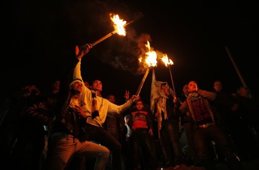 Palestinians hold torches as they celebrate the 48th anniversary of the founding of Fatah movement in Gaza City