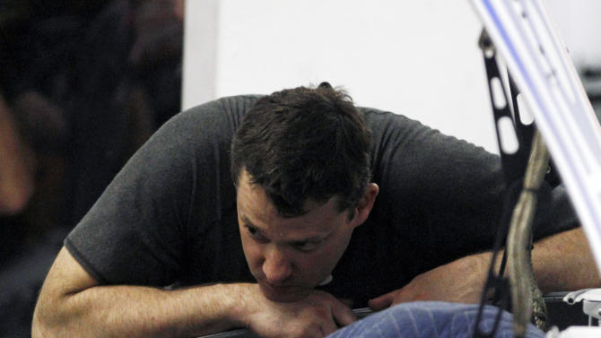 Tony Stewart looks under the hood of his car in the garage after he was involved in a crash during NASCAR auto race practice at Daytona International Speedway, Friday, Feb. 17, 2012, in Daytona Beach, Fla. (AP Photo/Reinhold Matay)