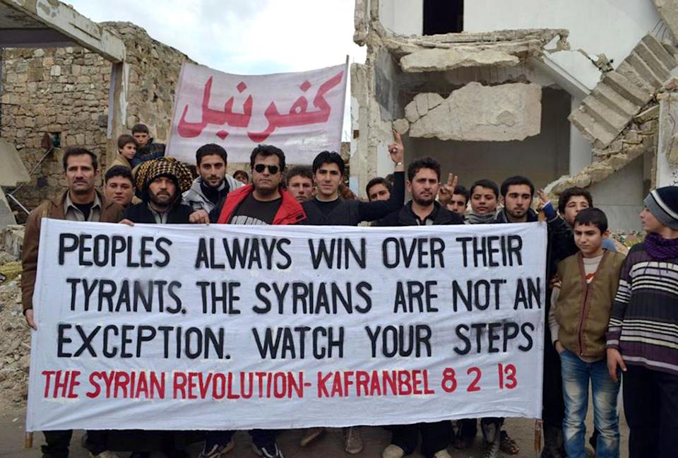 This citizen journalism image provided by Edlib News Network, ENN, which has been authenticated based on its contents and other AP reporting, shows anti-Syrian regime protesters holding a banner during a demonstration, at Kafr Nabil town, in Idlib province, northern Syria, Friday, Feb. 8, 2013. (AP Photo/Edlib News Network ENN)