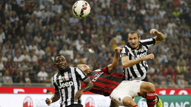 AC Milan's Keisuke Honda, center, challenge for the ball with Juventus's Kwadwo Asamoah, left, and Juventus's Giorgio Chiellini during the Serie A soccer match between AC Milan and Juventus at the San Siro stadium in Milan, Italy, Saturday, Sept. 20, 2014. (AP Photo/Antonio Calanni)
