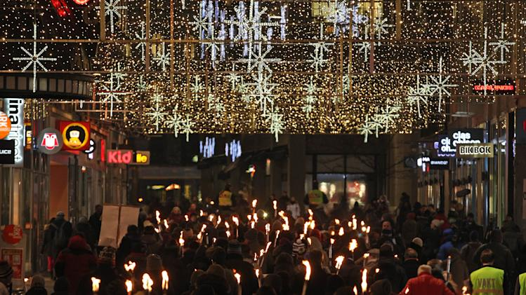 People walk with torches along a shopping street, to protest against the awarding to the Peace Prize to the EU bloc, in Oslo, Norway, Sunday Dec. 9, 2012.  The Nobel Peace Prize Committee awarded the prize to the European Union for its efforts to promote peace and democracy in Europe. (AP Photo/Yves Logghe)