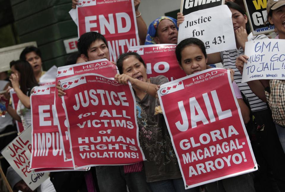 Activists hold slogans against former Philippine President Gloria Macapagal Arroyo as they await her release outside a government hospital in suburban Quezon City, north of Manila, Philippines, Wednesday July 25, 2012. Arroyo on Wednesday was released on bail after a judge found weak evidence linking her to an election sabotage case. (AP Photo/Aaron Favila)