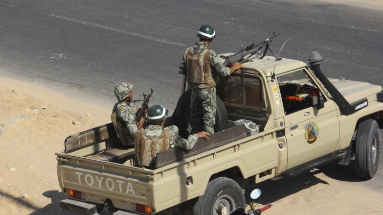 """Egyptian army personnel guard the road just outside Rafah, Egypt, Monday, Aug. 6, 2012. Egypt's military vowed on Monday to hunt down those behind the killing of at least 16 soldiers at a checkpoint along the Sinai border with Israel on Sunday Aug. 5, 2012. It called the attackers """"enemies of the nation"""" and suggested they were Egyptian Sinai-based militants who received Palestinian support from the Gaza Strip. (AP Photo)"""