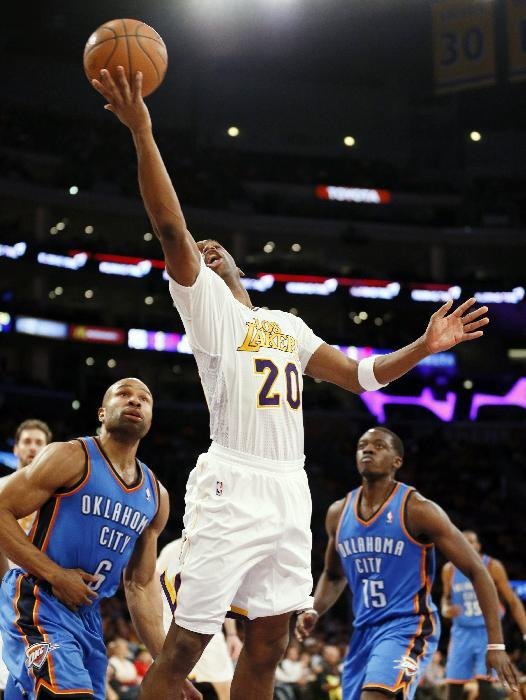 Los Angeles Lakers guard Jodie Meeks makes a reverse layup in front of Oklahoma City Thunder guard Derek Fisher, left, and guard Reggie Jackson during the second half of an NBA basketball game in Los