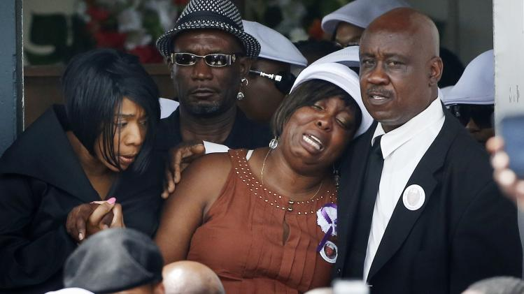 Odin Lloyd's mother, Ursula Ward, center, and his sister Olivia Thibou, left, leave the funeral ceremony for Lloyd at the Church of the Holy Spirit in Boston, Saturday, June 29, 2013. Hundreds of relatives, friends and well-wishers wept together and hugged at the funeral for Lloyd, a semi-pro football player whose killing led to murder and weapons charges against former New England Patriots player Aaron Hernandez. (AP Photo/Michael Dwyer)
