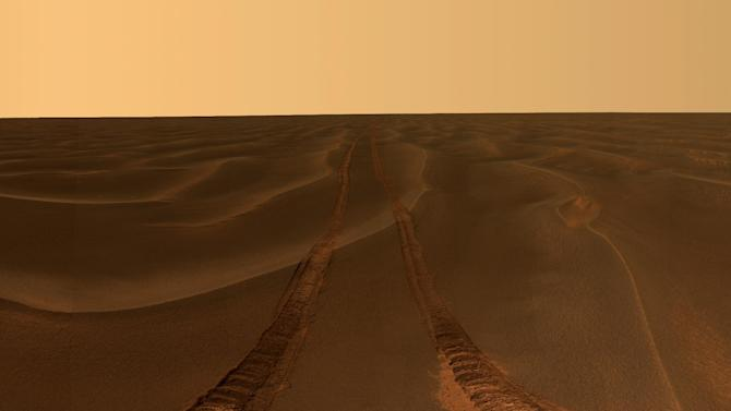 This image provided by NASA, shows rover tracks disappearing toward the horizon in a sea of sand between the craters Endurance and Victoria on the Meridiani Plains. Mars rover Opportunity took the image while stuck in the sand ripple dubbed Purgatory for over a month. Ten years after NASA landed two rovers on Mars on a 90-day mission, one rover is still exploring, and the project has generated hundreds of thousands of images from the Martian surface. Now the Smithsonian's National Air and Space Museum is presenting more than 50 of the best photographs from the two Mars rovers in an art exhibit curated by the scientists who have led the ongoing mission. (AP Photo/NASA/JPL-Caltech/Cornell University)