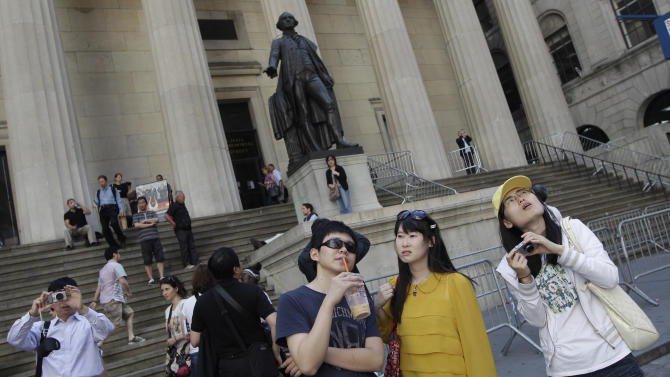 In this Friday, June 15, 2012, a group of tourists from China take in the sights of  the New York Stock Exchange and Federal Hall National Memorial. Major hotel brands are bending over backward to cater to the needs of the world's most sought-after traveler: the Chinese tourist. Now arriving on American shores in unprecedented numbers thanks to a streamlined visa process and a rising Chinese middle class, Chinese tourists are being treated to the comforts of home when they check in at the front desk. (AP Photo/Mary Altaffer)