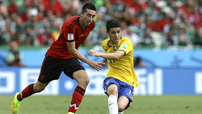 Brazil's Oscar, right, passes the ball as Mexico's Marco Fabian closes in during the group A World Cup soccer match between Brazil and Mexico at the Arena Castelao in Fortaleza, Brazil, Tuesday, June 17, 2014. (AP Photo/Martin Mejia)