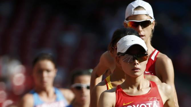 Lu Xiuzhi of China (R) leads the pack as athletes compete in the women's 20 km race walk final during the 15th IAAF World Championships at the National Stadium in Beijing