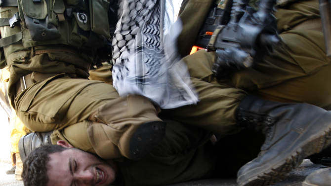 A Palestinians activist is detained by Israeli soldiers during a protest against the Prawer Plan to resettle Israel's Palestinian Bedouin minority from their villages in the Negev Desert, near the Israeli settlement of Bet El, north of the West Bank city of Ramallah, Saturday, Nov. 30, 2013. (AP Photo/Majdi Mohammed)