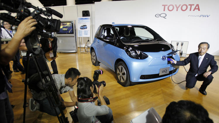 """Toyota Motor Corp. Vice Chairman Takeshi Uchiyamada poses for photographers as he puts a plug to the newly-developed compact electric vehicle """"eQ"""" during a press conference in Tokyo Monday, Sept. 24, 2012. Toyota is boosting its green vehicle lineup, with plans for 21 new hybrids in the next three years, a new electric car later this year and a fuel cell vehicle by 2015 in response to growing demand for fuel efficient and environmentally friendly driving. (AP Photo/Koji Sasahara)"""