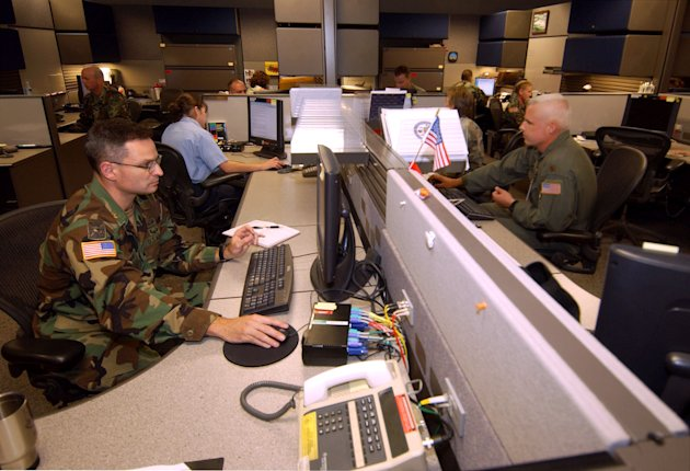 FILE - This Aug. 25, 2004 file photo shows unidentified analysts at the Combined Intelligence and Fusion Center for NORAD/Northcom in Colorado Springs, Colo. A multibillion-dollar information-sharing program that was created in the aftermath of 9/11 has improperly collected information about innocent Americans and produced no valuable intelligence on terrorism, according to a Senate report that describes an effort that ballooned far beyond anyones ability to control. (AP Photo/David Zalubowski/File)