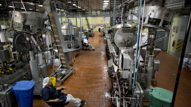 In this Thursday, March 26, 2015 photo, workers keep an eye on the production line at the Santa Teresa rum factory in La Victoria, Aragua State, Venezuela. Key to its success are stringent laws that demand rum be aged for at least two years. And unlike more arid sugar-growing parts of the Caribbean, local rum makers say the fertile soil and cooler climate in the best rum-growing area outside Caracas lends Venezuelan rum a rounder, more flavorful aroma. (AP Photo/Ariana Cubillos)