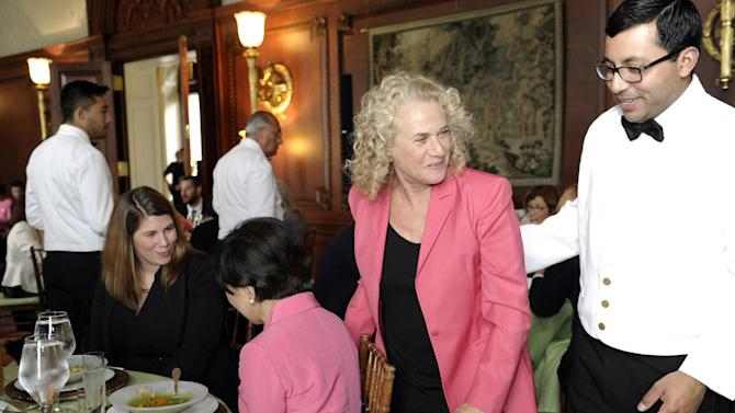 "Singer-songwriter Carole King, second from right, walks past Rep. Doris Matsui, D-Calif., center, during a luncheon at the Library of Congress in Washington, Tuesday, May 21, 2013, to honor King.  Carole King isn't done with music — not yet anyway. The 71-year-old singer-songwriter known for such hits as ""(You Make Me Feel Like) A Natural Woman"" and ""You've Got A Friend"" is being awarded the nation's highest prize for popular music Tuesday. She'll receive the Gershwin Prize for Popular Song at the Library of Congress and will be honored Wednesday by President Barack Obama at the White House. (AP Photo/Susan Walsh)"