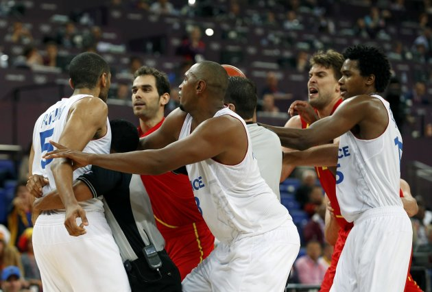 France's Nicolas Batum (L) is held back by officals after a hard foul in his game against Spain at their men's quarterfinal basketball match at the North Greenwich Arena in London during the London 2012 Olympic Games August 8, 2012.                   REUTERS/Mike Segar (BRITAIN  - Tags: SPORT OLYMPICS SPORT BASKETBALL)