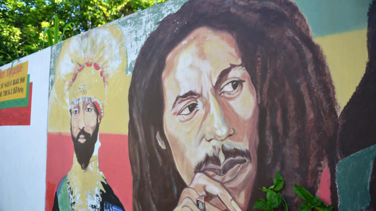 A mural depicting reggae music icon Bob Marley, right, and former Ethiopia's Emperor Haile Selassie decorate a wall in the yard of Marley's Kingston home, in Jamaica, Wednesday, Feb. 6, 2013. Relatives and old friends, joined by hundreds of tourists, celebrated Marley's 68th birthday, in the yard of his his Kingston. The reggae icon died of cancer in 1981 at age 36. (AP Photo/ David McFadden)