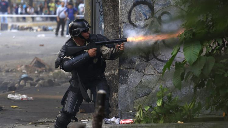 A national policeman fires tear gas at anti-government protesters hiding in a building during a protest in Caracas