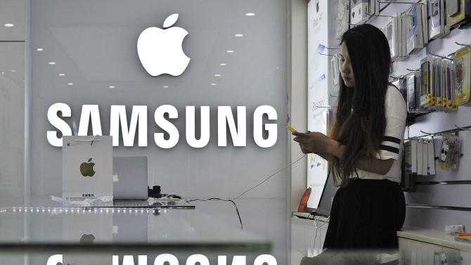 File photo of a sales assistant using her mobile phone next to the company logos of Apple and Samsung at a store in Hefei