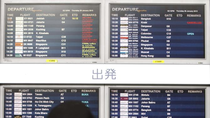 A traveler checks out the departure board at Kuala Lumpur International Airport, in Malaysia, Thursday, Jan. 29,  2015. Malaysia's Civil Aviation Authority officially declared the MH370 crash an accident on Thursday, fulfilling a legal obligation that will allow efforts to proceed with compensation claims. (AP Photo/Joshua Paul)