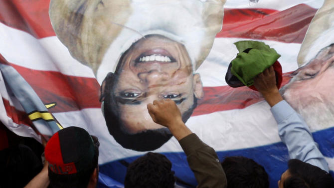 Pakistani protesters hold a banner depicting U.S. President Barack Obama and pastor Terry Jones during a rally in Peshawar, Pakistan as a part of widespread anger across the Muslim world about a film ridiculing Islam's Prophet Muhammad, on Thursday, Sept. 20, 2012. Hundreds of Pakistanis angry at an anti-Islam film that denigrates the religion's prophet clashed with police in the Pakistani capital Thursday, the most violent show of anger in a day that saw smaller demonstrations in Indonesia, Iran and Afghanistan. (AP Photo/Mohammad Sajjad)