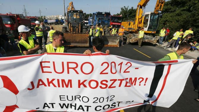 Workers block the road leading to the Arena stadium in Gdansk, Poland, Monday, June 18, 2012. The workers are protesting as they were not paid for building the stadium, which hosts the Euro 2012 soccer championships games. The banner reads: Euro 2012 At what costs?. (AP Photo/Czarek Sokolowski)
