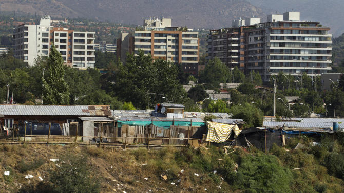 """Luxury apartment buildings in Las Condes' neighborhood are seen at background as the San Pablo shanty town is seen at front in Santiago, Chile, Wednesday, Jan. 23, 2013.  European, Latin American and Caribbean leaders gathering for this weekend's economic summit will likely see only one side of Chile _ the polished, upscale country where tourists and investors stay in five-star hotels in a sparklingly clean financial district nicknamed """"Sanhattan,"""" well away from Santiago's slums. (AP Photo/Victor R. Caivano)"""