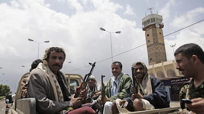 Yemeni policemen sit in a pickup truck in front of Sanaa's International airport in Yemen, Sunday, April 8, 2012. Yemen's main airport reopened on Sunday, a day after gunmen loyal to the nation's former president seized the facility in the capital Sanaa, officials said. Saturday's assault on the airport involved armed tribesmen along with troops in uniform. Driving pickup trucks mounted with anti-aircraft guns, they blasted buildings of Yemen's main airport and opened fire on one of the airport surveillance towers before surrounding the entire complex, blocking roads and turning away passenger vehicles. (AP Photo/Hani Mohammed)