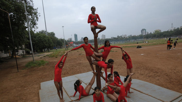 "Girls practise a Mallakhamb ""pyramid"" pose in the shape of a crown while suspended at the Shree Samartha Vyayam Mandir in Mumbai"