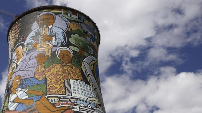 A giant portrait of former president Nelson Mandela, center right, adorns a cooling tower of a now defunct power station in Soweto, South Africa, Monday, Dec 10, 2012. Mandela underwent more unspecified medical tests in a military hospital in Pretoria, South Africa, as the public and journalists outside continued to ask the same as of yet unanswered questions: What, if anything, is wrong with the 94-year-old anti-apartheid icon.  (AP Photo/Denis Farrell)