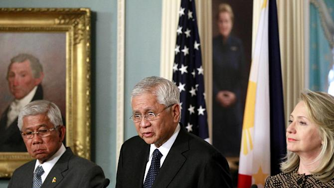 FILE - Philippines' Secretary of Foreign Affairs Albert del Rosario, center, with Secretary of National Defense Voltaire Gazmin, left, speaks at a news conference at the U.S. Department of State with U.S. Secretary of State Hillary Rodham Clinton in Washington. The U.S. increased military aid to the Philippines and resolved to help its ally on maritime security. The steps came as the country is locked in a standoff with China over competing territorial claims in the South China Sea. (AP Photo/Haraz N. Ghanbari, File)