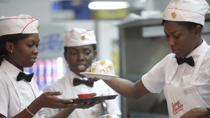 In this photo taken Wednesday, Jan. 23, 2013 waitresses prepare to serve hamburgers  and fries at Johnny Rockets restaurant in Lagos, Nigeria. As Nigeria's middle class grows along with the appetite for foreign brands in Africa's most populous nation, more foreign restaurants and lifestyle companies are entering the country. And the draw on Nigerians' new discretionary spending has also put new expectations on providing quality service in a nation where many have grown accustomed to expecting very little. ( AP Photo/Sunday Alamba)