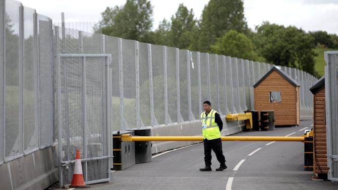 A security person patrols a check point close to The Lough Erne Golf Resort Enniskillen, Northern Ireland, Thursday, June 13, 2013.  The Resort  is due to host the G8 summit on the 17th and 18th June.  (AP Photo/Peter Morrison)