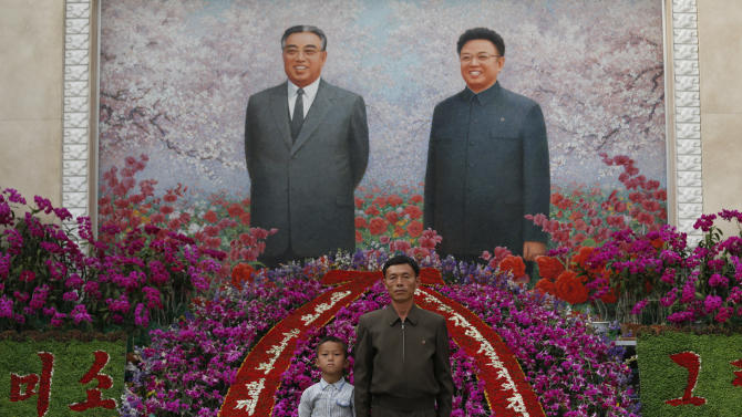 """A man and a boy pose for a picture in front of portraits of the late leaders Kim Il Sung and Kim Jong Il at a festival for the """"Kimilsungia"""" flower to mark 100 years since the birth of North Korea's late leader in Pyongyang, North Korea, Tuesday, April 17, 2012. (AP Photo/Vincent Yu)"""