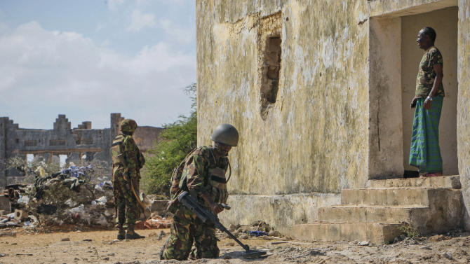 In this photo released by the African Union-United Nations Information Support Team, a team of engineers serving with the Kenyan contingent of the African Union Mission in Somalia (AMISOM) use metal detectors as they search for improvised explosive devices in Kismayo, southern Somalia, Wednesday, Oct. 3, 2012. Allied African troops have taken full control of Kismayo in Somalia, the last stronghold of al-Shabab Islamist rebels who have been fighting against the country's internationally backed government, with Kenya Defence Forces and the Somali National Army now patrolling the streets. (AP Photo/AU-UN IST, Stuart Price)