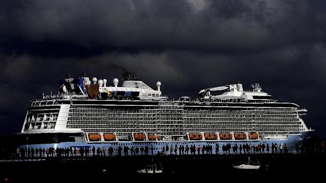 The Royal Caribbean cruise ship Anthem of the Seas is dramatically lit against a louring sky as a crowd of onlookers watch the cruise ship departing the dock at Southampton, England, Sunday May 3, 2015. (Steve Parsons / PA via AP) UNITED KINGDOM OUT - NO SALES - NO ARCHIVES