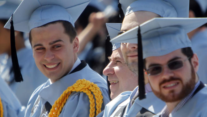 Columbia University janitor Gac Filipaj, second from left, smiles while listening to a speech during the Columbia University School of General Studies graduation ceremony, Sunday, May 13, 2012, in New York. Filipaj, an ethnic Albanian who left his native Montenegro 20 years ago to escape war, is graduating with honors after 12 years of balancing studies and his full-time job. (AP Photo/Jason DeCrow)