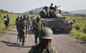 Congolese army soldiers march past a tank aimed towards …