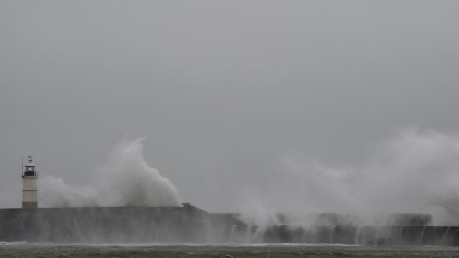 Waves crash against the harbour wall and light beacon at Newhaven in southern England.