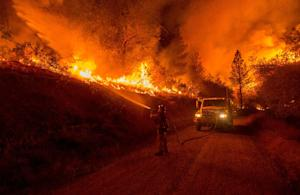 A firefighter douses flames from a backfire while battling…
