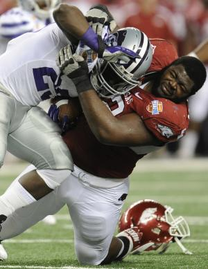 Arkansas defensive tackle DeQuinta Jones (92) tackles Kansas State running back Angelo Pease (29) during the first half of the Cotton Bowl NCAA college football game, Friday, Jan. 6, 2012, in Arlington, Texas. (AP Photo/Matt Strasen)