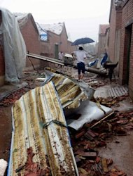 <p>Residents making their way home through debris as a storm hits in Beijing. The death toll from the heaviest rain to hit Beijing in over 60 years has risen to 37, Chinese state media reported on Sunday.</p>