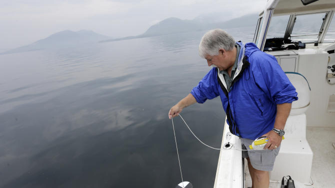 "Larry Eichler, a researcher scientist for Rensselaer Polytechnic Institute's Darrin Fresh Water Institute, lowers a Secchi disk into Lake George to test light penetration on Wednesday, June 26, 2013, in Bolton Landing, N.Y. An unprecedented project to turn New York's Lake George into the ""smartest lake in the world"" is being launched to monitor the lake from its sun-dappled shores to its dark depths in hopes of keeping the Adirondack attraction pristine. (AP Photo/Mike Groll)"