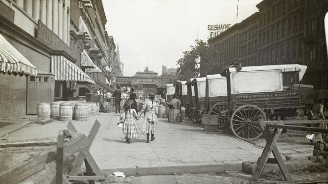 In this circa 1890 photo provided by the New York City Municipal Archives, a pair of girls walk east along 42nd Street in New York. Acker, Merrall and Condit wine shop delivery wagons are on the right and the C.C. Shayne Furrier sign can be seen on the roof overhead. Over 870,000 photos from an archive that exceeds 2.2 million images have been scanned and made available online, for the first time giving a global audience a view of a rich collection that documents life in New York City.  (AP Photo/New York City Municipal Archives, DeGregario Collection (New York Camera Club)) MANDATORY CREDIT
