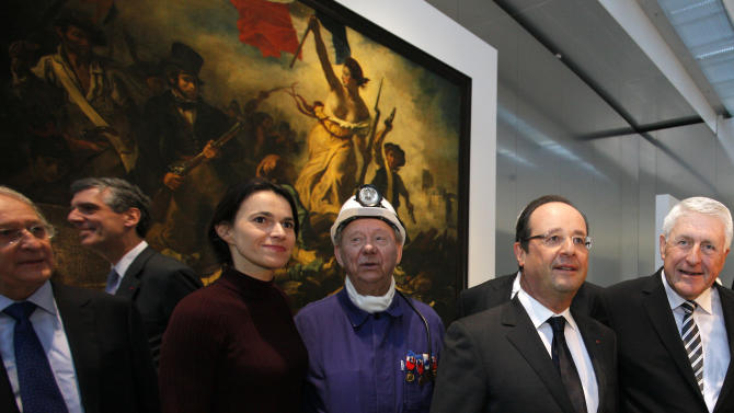 """France's President Francois Hollande, second right, is seen with  Culture minister Aurelie Filippetti, third left,  with a former miner, Lucien Laurent, centre in front of """" La Liberte Guidant le Peuple"""", a painting by Eugene Delacroix during the inauguration of the Louvre Museum in Lens, northern France, Tuesday, Dec. 4, 2012. The museum in Lens is to open on Dec. 12, as part of a strategy to spread art beyond the traditional bastions of culture in Paris to new audiences in the provinces. (AP Photo/Michel Spingler Pool)"""